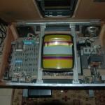 Il Taito T.T.Block aperto. Alla sinistra il set di schede logiche, al centro il monitor in bianco e nero con le raster bars colorate appicicate sopra, sulla destra il gruppo di alimentazione.